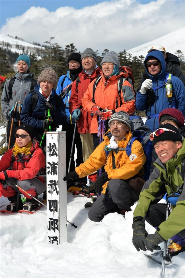 原始ケ原の登山道沿いにある「松浦武四郎通過の地」の標柱を囲み、写真に納まる参加者。実際に武四郎が歩んだルートはここから2キロほど離れている