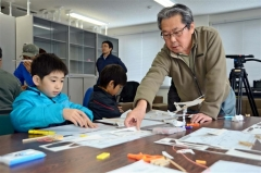 紙飛行機を飛ばす会の指導を受けながら制作する子供たち