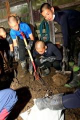 倉庫の中にたまった泥を袋に入れる部員たち(22日午後1時15分ごろ、清水町旭山で)