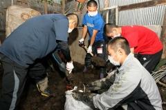 倉庫の中にたまった泥を袋に入れる部員たち(22日午後1時半ごろ、清水町旭山で)
