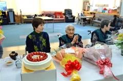 110歳の誕生日への贈り物に手を合わせる千葉タリさん(中央)