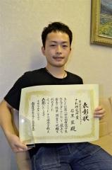 表彰状と副賞のクリスタルトロフィーを手にする石黒さん