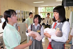 人形で赤ちゃんの抱き方を学ぶ参加者
