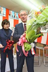 6選を無投票で決め、受け取った花束を掲げる小林康雄氏(左は孝子夫人)