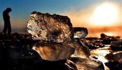 朝日に照らされて砂浜で輝く「ジュエリーアイス」(30日午前7時20分ごろ、豊頃町大津、金野和彦撮影)