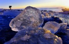 朝日に照らされ砂浜で輝く「ジュエリーアイス」(30日午前6時50分ごろ、豊頃町大津、金野和彦撮影)