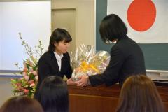 同窓会から花束を受け取る新入生(左)