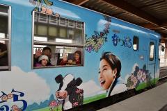広瀬すずさん演じるヒロインが描かれたラッピング列車に乗り込み出発する家族連れ(27日午前9時半ごろ、道の駅オーラタウン93りくべつ。金野和彦撮影)