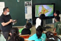 モニターに写し出した副読資料で学ぶ児童