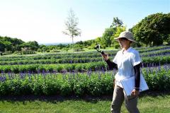 スマートフォンで撮影しながら、ガーデン内をガイドをする高田玲子ヘッドガーデナー(1日、金野和彦撮影)