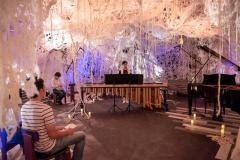 羊毛アートによる幻想的空間の中でマリンバ演奏を披露する左藤さん(中央)