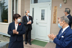空き家を活用して新たに開所した「緑街ふれあいの家」。拍手して喜ぶ(右奥から時計回りに)長井町内会長、編田代表、河田会長、小野町長