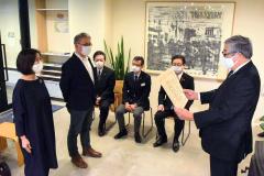 稲野理事長(右)から表彰を受ける(左から)坂口社長、柏尾氏
