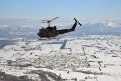 大雪山系をバックに飛行する「UH―1」。眼下に鹿追市街地が見える