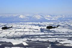 大雪山系をバックに飛行する「UH―1」