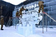 自衛隊員が仕上げに取り組む氷のレリーフ。写真撮影用に氷の椅子も制作した(25日午前10時ごろ)