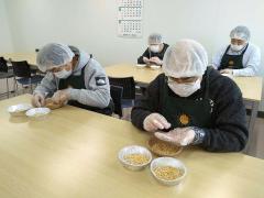 トウモロコシの選別作業を行う「まある」の通所者(ふたみ青果提供)