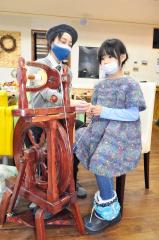 紡毛機で糸紡ぎを体験した参加者と伊藤さん(左)