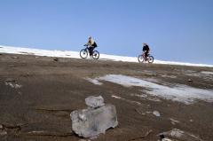 波打ち際に打ち上げられたジュエリーアイスを横目に、自転車で海岸を巡る参加者