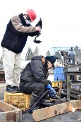 廃棄物処理の作業風景を撮影する漆原さん(左、タナベで)