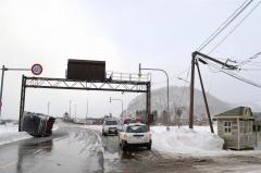 強風で横転したトラック(左)と折れた電柱(広尾町音調津、16日午後3時ごろ)