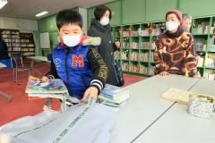 借りた本をバッグに詰める子ども。大空市民の会のメンバーが見守る