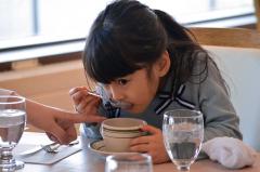 スプーンを使ってスープを口にする園児