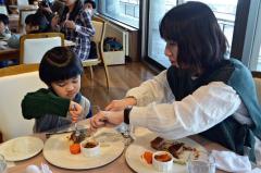 慣れない手付きでナイフとフォークを扱う園児と指導する母親
