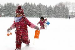 雪の上を元気に走る子どもたち