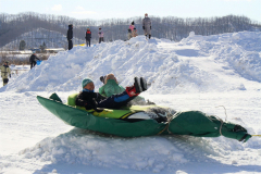 ラフティングボートに乗って楽しむ児童たち