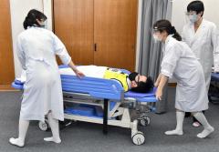 ワクチンの接種後に急病者が出たと想定して搬送する看護師ら(塩原真撮影)