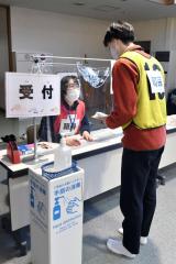 ワクチン接種の受け付けをする町民役の職員(塩原真撮影)