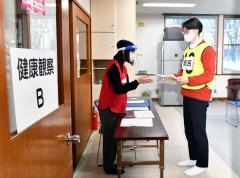 町民役の職員に接種済み証を手渡す町職員(塩原真撮影)