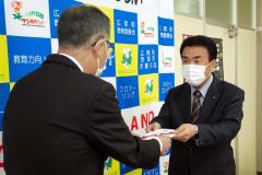目録を菅原教育長(左)に手渡す亀田副会長