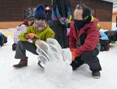 帯広清川小の6年生に、氷の白鳥の削り方を教える一ノ瀬さん(右。2月18日、小山田竜士撮影)