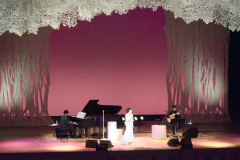 切り絵アーティストの柴田あゆみさんの切り絵で飾り付けたステージで美声を披露する森山良子さん(中央)