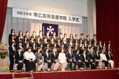 記念撮影する新入生と教職員
