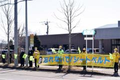 旗や横断幕を手に交通安全を呼び掛ける参加者