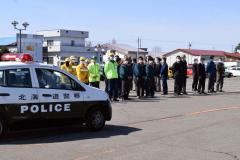 出動する警察車両を見送る参加者