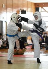 【小学1~3年混合の部決勝】ハイキックを狙う小林美羽子(右)。効果1を奪い優勢勝ちした