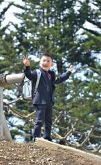 「ママこっちだよ-」。入学式が終わり、校庭の丘に登り遊ぶ新1年生(帯広緑丘小、塩原真撮影)