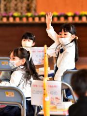 「わたしはここよ」。入学式が始まる前に、父母に手を振る新入学児童(帯大空小。金野和彦撮影)