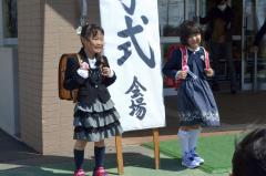 玄関前の看板と一緒に笑顔で記念撮影(大樹小、松村智裕撮影)