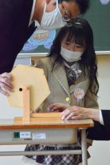 ガラポン 入学式後のホームルームで自己紹介した後に担任の吉野友晴先生が作ったガラポン抽選器でくじ引きをする新1年生(音更駒場小)