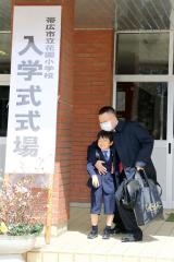 父親に抱きしめられ、玄関前で記念写真に納まる新入生(帯広花園小で、後藤貴子通信員撮影)