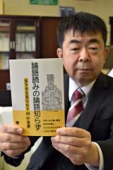 論語の教えを日常生活と結びつけて紹介した著書を手にする秦校長