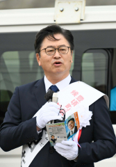 選挙事務所前で第一声をする按田氏(13日午前8時50分ごろ。金野和彦撮影)