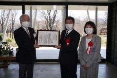 磯田理事長(左)から表彰状を受け取る宮嶋代表(中央)と京子さん(右)