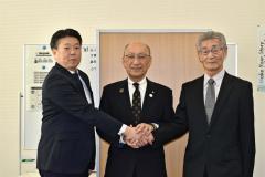 協定を交わし握手する澤田校長(左)と笠谷理事長(右)。中央は飯田町長