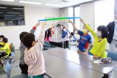 「協力」について、フラフープを持ち上げて実感する子どもたち